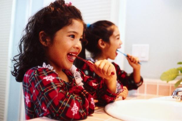 Two little girls brushing their teeth.